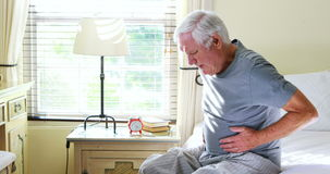 Unhappy senior man suffering from stomach ache. At home stock footage