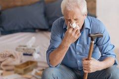 Unhappy senior man using a paper tissue Stock Photos