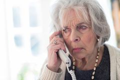 Worried Senior Woman Answering Telephone At Home. Unhappy Senior Woman Answering Telephone At Home royalty free stock photography