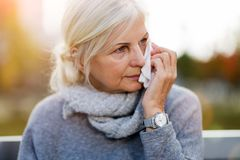 Weeping old woman wipes her eyes with tissue. Unhappy senior woman wipes her eyes with a tissue royalty free stock images