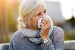 Weeping old woman wipes her eyes with tissue. Unhappy senior woman wipes her eyes with a tissue royalty free stock photos