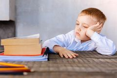Unhappy serious boy looking at his textbooks royalty free stock images