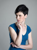 Unhappy short hair beauty looking away squinting eyes. Over gray studio background Royalty Free Stock Image