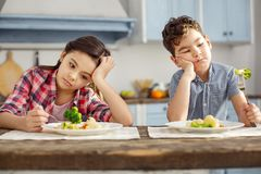 Unhappy siblings looking sadly at the vegetables. We hate vegetables. Attractive sad dark-haired little brother and sister sitting at the table and having Stock Photography