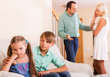 Unhappy siblings and quarrel parents. Unhappy young siblings waiting when parents stop screaming at home Stock Photos