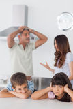 Unhappy siblings sitting in kitchen with their parents who are a Stock Images