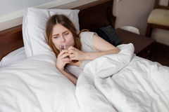 Unhappy sick girl lying on bed drink water from glass Royalty Free Stock Photography