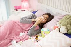 Sick hispanic female teenager in bed sneezing Royalty Free Stock Photography