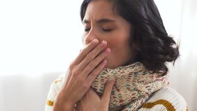 Unhappy sick woman in scarf coughing at home. Cold and health problem concept - unhappy woman in scarf coughing at home stock video footage