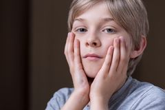 Unhappy small kid. Close up of unhappy small kid holding face between hands Royalty Free Stock Images