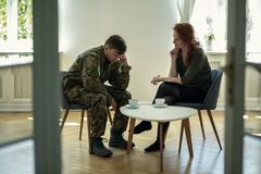 Unhappy soldier in green uniform and psychotherapist during consultation in the office. Concept royalty free stock image