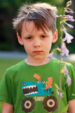 Unhappy somber little 5 year old boy. A closeup of a somber little 5 yr old boy in green shirt and disheveled dark hair. Shallow depth of field, selective focus Stock Photo