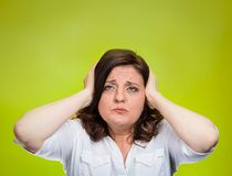 Unhappy stressed woman covering ears looking up Stock Image