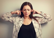 Unhappy stressed young woman not want to listen and covering the. Ears her fingers. Vintage toned portrait royalty free stock photography