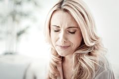 Unhappy stressful woman sitting closing her eyes. Help me somebody. Unhappy stressful blonde woman sitting in the bright room being alone closing her eyes Stock Photos