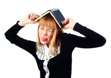 Unhappy student. Upset young student with a book on her head, unwilling to study Stock Photography