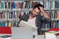 Unhappy Student With Too Much to Study. Stressed Student in High School Sitting at the Library Desk Royalty Free Stock Photo