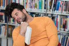 Unhappy Student With Too Much to Study. Stressed Young Male Student Reading Textbook While Sitting in Library Royalty Free Stock Photo