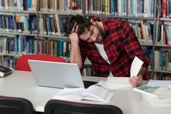 Unhappy Student With Too Much to Study. Stressed Young Male Student Reading Textbook While Sitting in Library Stock Images