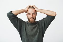 Unhappy swedish young man with beard holding hands on head with frightened expression trying to remember if he turn off Stock Image