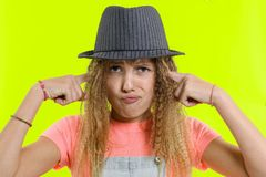 Unhappy teen girl covered her ears, over yellow studio background stock image