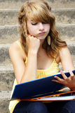Unhappy teen student. Unhappy or frustrated young blond teenager girl going back to school or looking at her homework in a binder Royalty Free Stock Photo