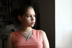 Unhappy teen by the window royalty free stock images