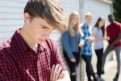 Unhappy Teenage Boy Being Gossiped About By Peers stock photo