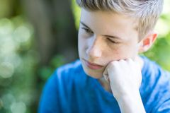 Close Up Of Unhappy Teenage Boy Sitting Outdoors royalty free stock images