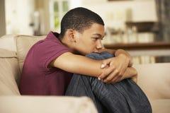 Unhappy Teenage Boy Sitting On Sofa At Home Stock Photos