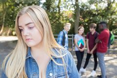 Unhappy Teenage Girl Being Gossiped About By School Friends stock photography