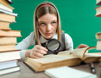 Unhappy teenage girl with magnifying glass surrounded by lots of books Royalty Free Stock Image