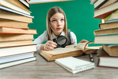 Unhappy teenage girl with magnifying glass surrounded by lots of books Royalty Free Stock Photos