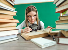 Unhappy teenage girl with magnifying glass. Surrounded by lots of books / photo of teen school girl, creative concept with Back to school theme Stock Photography