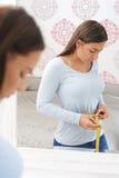 Unhappy Teenage Girl Measuring Waist