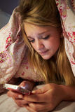 Unhappy Teenage Girl Sending Text Message Whilst Lying In Bed Stock Images