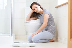Unhappy Teenage Girl Sitting On Floor With Bathroom Scales Royalty Free Stock Photo