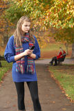 Unhappy Teenage Girl Standing In Autumn Park. With Couple On Bench In Background Stock Photos
