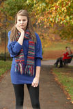 Unhappy Teenage Girl Standing In Autumn Park. With Couple On Bench In Background Royalty Free Stock Photos