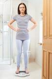 Unhappy Teenage Girl Standing On Bathroom Scales