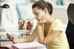 Unhappy Teenage Girl Studying At Desk In Bedroom Looking At Mobile Phone Stock Photos