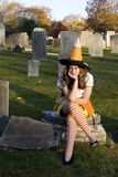 Unhappy Teenage Halloween Witch in Graveyard. Young adolescent girl (13 yrs. old) with teen attitude (looking unhappy) dressed in orange and white Halloween Stock Image
