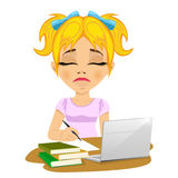 Unhappy teenage schoolgirl doing her homework with laptop and books on desk Royalty Free Stock Photo