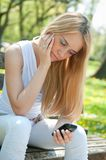 Unhappy teenager with mobile phone Royalty Free Stock Photo