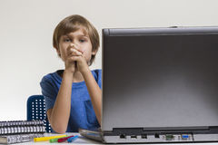 Unhappy tired bored boy sitting near laptop pc. Stock Photo