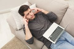 Overworking man suffering from headache at home office. Unhappy tired man with laptop on couch at home office, suffering from headache, above view Stock Photo
