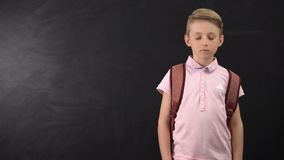 Unhappy tired schoolboy standing near chalkboard, suffering overload at school. Stock footage stock video footage