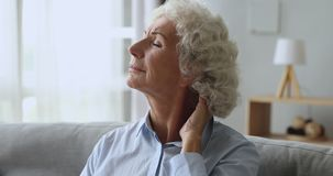 Unhappy tired senior woman rubbing neck feeling pain at home