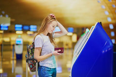 Unhappy tourist girl in international airport, doing self check-in Stock Image