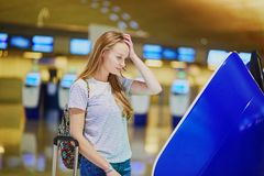 Unhappy tourist girl in international airport, doing self check-in royalty free stock photos